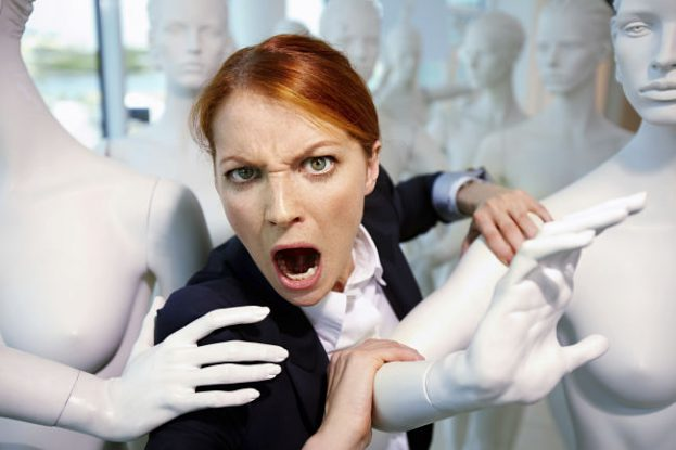 Portrait of a woman shouting among mannequins